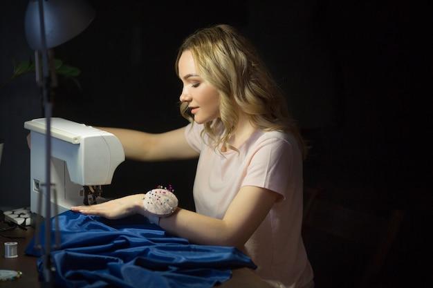 Hermosa joven cose un vestido en una máquina de coser por la noche en el trabajo