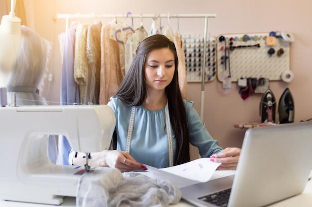 Hermosa joven costurera o modista usando una computadora portátil y trabajando para un vestido nuevo en su propio taller.