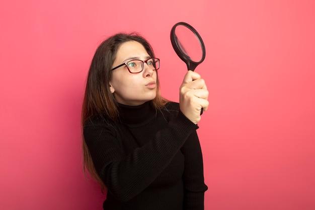 Hermosa joven en un cuello alto negro y gafas mirando algo a través de una lupa con cara seria