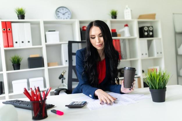 Una hermosa joven cuenta con una mano en la calculadora, en su segunda mano sostiene un vaso con café