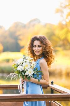 Hermosa joven dama de honor con pelo largo y rizado