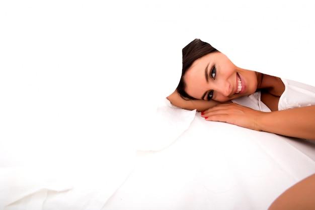 Una hermosa joven debajo de las sábanas en la cama