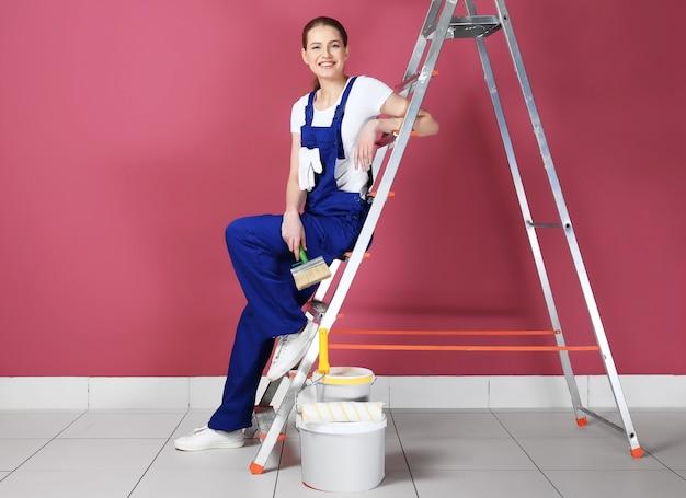 Hermosa joven decoradora sentada en la escalera en la habitación vacía