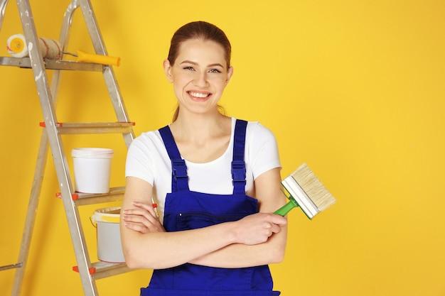 Hermosa joven decoradora sobre fondo de color