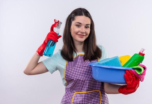 Hermosa joven en delantal y guantes de goma con lavabo con herramientas de limpieza y spray de limpieza sonriendo confiado