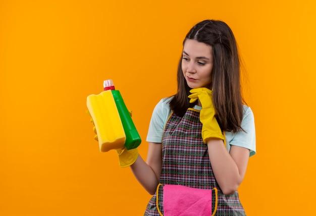 Hermosa joven en delantal y guantes de goma con productos de limpieza y una esponja mirándolos con expresión pensativa, tratando de tomar una decisión