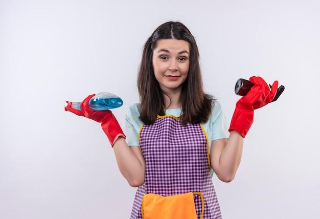 Hermosa joven en delantal y guantes de goma sosteniendo aerosoles de limpieza mirando confundido e incierto encogiéndose de hombros
