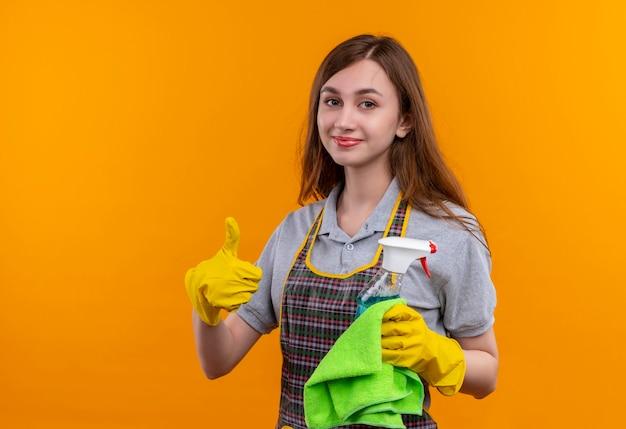 Hermosa joven en delantal y guantes de goma con spray de limpieza y alfombra mirando a la cámara sonriendo mostrando los pulgares para arriba, listo para limpiar