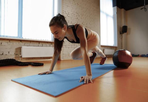 Hermosa joven delgada haciendo algo de gimnasia en el gimnasio con medball. atleta, deporte, cuerda, entrenamiento, entrenamiento, ejercicios y concepto de estilo de vida saludable