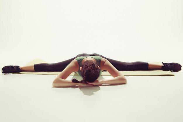 Hermosa joven delgada haciendo ejercicios de estiramiento en el gimnasio contra blanco