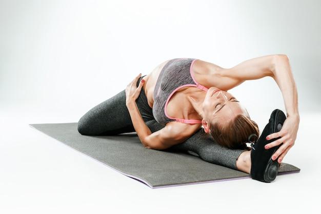 Hermosa joven delgada haciendo ejercicios de estiramiento en el gimnasio contra un blanco