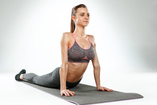 Hermosa joven delgada haciendo ejercicios de estiramiento en el gimnasio contra el fondo blanco.
