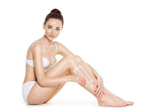 Hermosa joven depilarse las piernas con cera - estudio sobre fondo blanco.