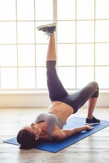 Hermosa joven deportista está haciendo yoga en el gimnasio
