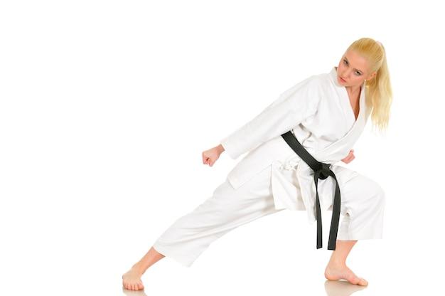 Hermosa joven deportista rubia de karate en un kimono hace una posición para comenzar a entrenar