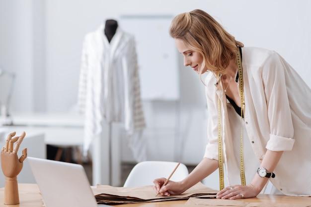 Hermosa joven desarrollando una nueva prenda de vestir, escribiendo sobre patrones acostado sobre una mesa con una computadora portátil y una mano de maniquí sobre ella.