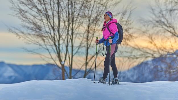 Hermosa joven descansa durante una caminata con raquetas de nieve