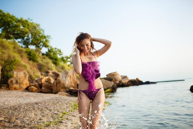 Hermosa joven descansa en la playa de la mañana