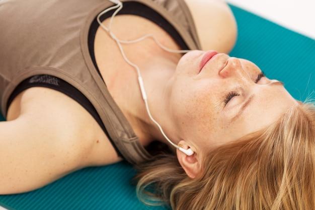 Hermosa joven descansando después del entrenamiento con auriculares en los oídos