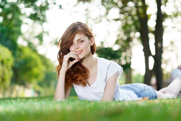 Hermosa joven descansando en la hierba verde fresca