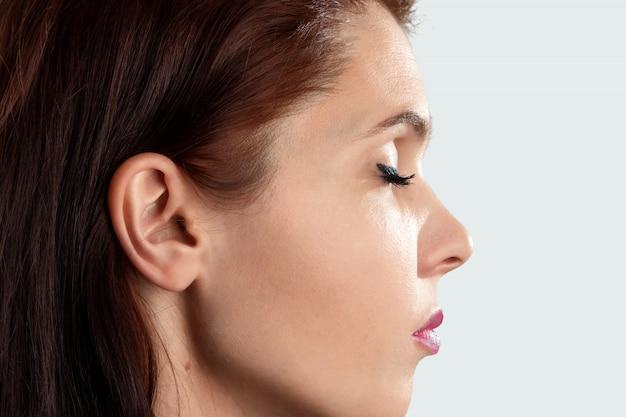 Hermosa, joven detalle de la cabeza con el primer plano femenino de oreja y cabello humano, retrato en perfil.