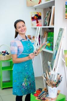 Hermosa joven dibuja una imagen pinta en la lección de arte