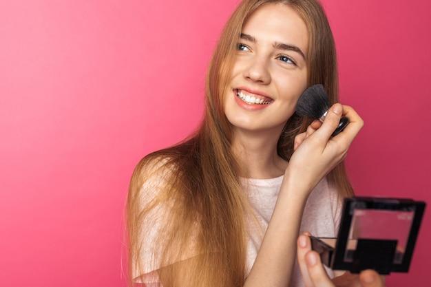 Hermosa joven disfruta de pincel y polvo y se mira en el espejo, hace maquillaje
