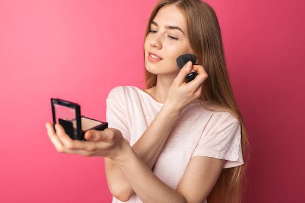 Hermosa joven disfruta de pincel y polvo y se mira en el espejo, hace las paces, chica con el pelo largo y rubio