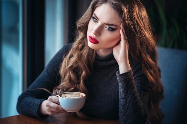 Hermosa joven disfrutando de café capuchino con espuma junto a la ventana en un café