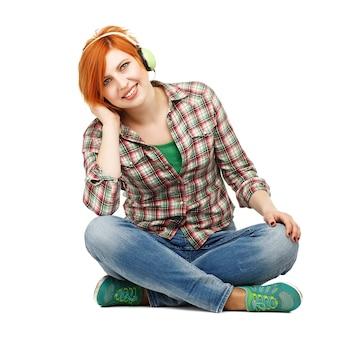 Hermosa joven disfrutando de escuchar música en auriculares aislado en blanco