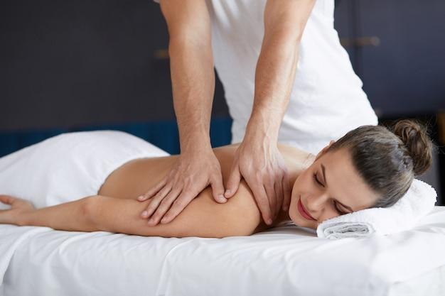 Hermosa joven disfrutando de masaje de espalda y hombros en spa