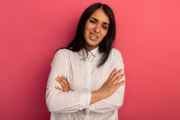 Hermosa joven disgustada con camiseta blanca cruzando las manos aisladas en rosa