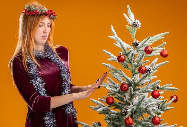 Hermosa joven disgustada de pie cerca del árbol de navidad con vestido rojo y corona con guirnalda en el cuello sosteniendo las manos en el árbol aislado sobre fondo naranja