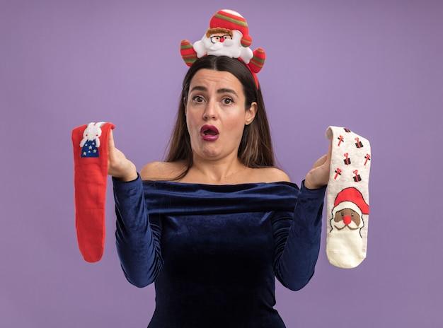 Hermosa joven disgustada con vestido azul y aro de pelo de navidad sosteniendo calcetines de navidad aislado sobre fondo púrpura