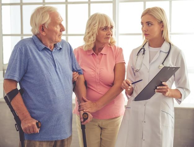 Hermosa joven doctora está hablando con la pareja de ancianos.
