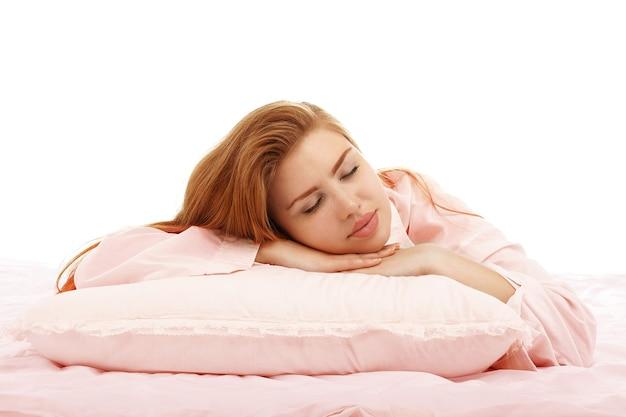 Hermosa joven duerme en la cama abrazando una almohada en su estómago