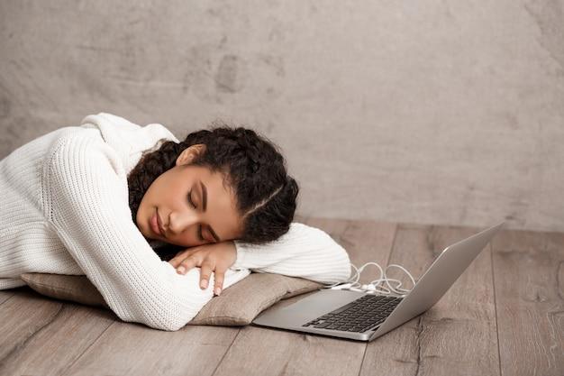 Hermosa joven durmiendo en la almohada en el piso cerca de la computadora portátil