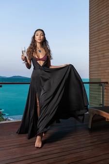 Hermosa joven elegante en un hermoso vestido de noche de chocolate con una enorme joyería azul en el cuello posando en la terraza