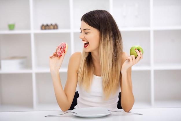 Hermosa joven eligiendo entre comida sana y comida chatarra