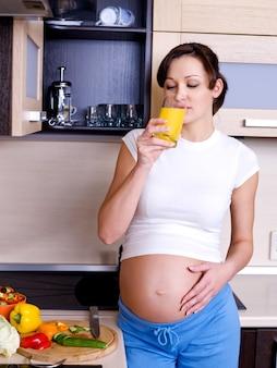 Hermosa joven embarazada está en la cocina y bebe el jugo de naranja