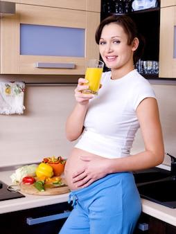 Hermosa joven embarazada está en la cocina con un vaso de jugo de naranja