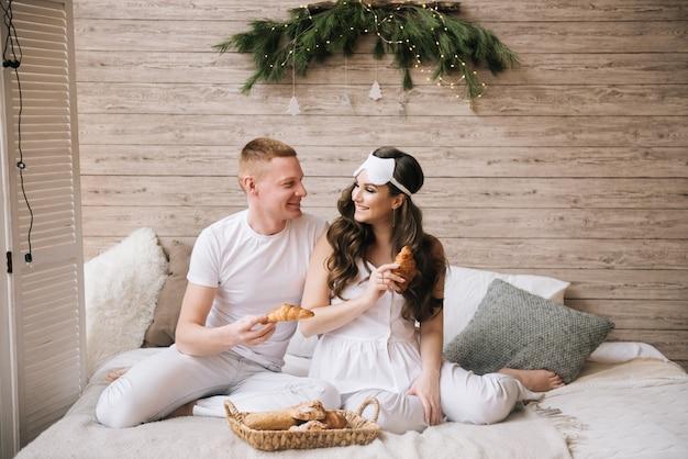 Hermosa joven embarazada elegante, con marido desayunando cruasanes en la cama