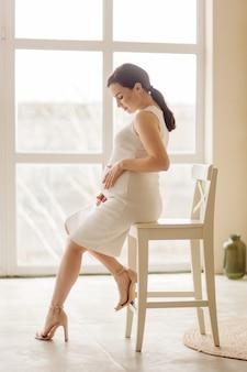 Hermosa joven embarazada posando en estudio en vestido