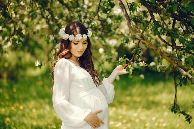 Hermosa joven embarazada en un vestido blanco largo y corona sobre su cabeza