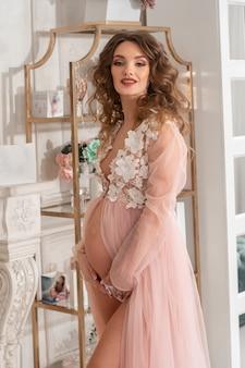 Hermosa joven embarazada con un vestido rosa en casa