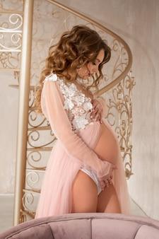 Hermosa joven embarazada en vestido rosa