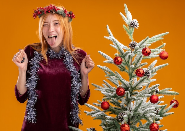 Hermosa joven emocionada de pie cerca del árbol de navidad con vestido rojo y corona con guirnalda en el cuello mostrando la lengua y haciendo gesto de sí aislado en la pared naranja