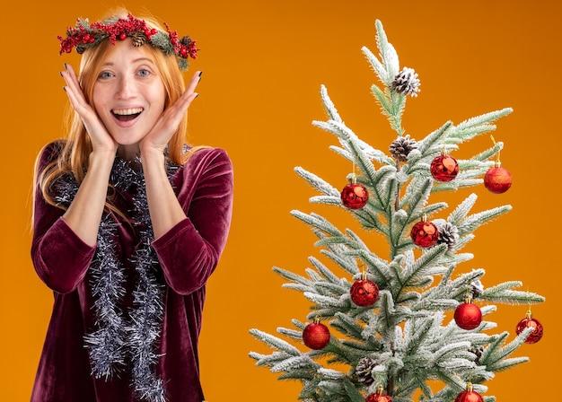 Hermosa joven emocionada de pie cerca del árbol de navidad con vestido rojo y corona con guirnalda en el cuello tomados de la mano alrededor de la cara aislada en la pared naranja