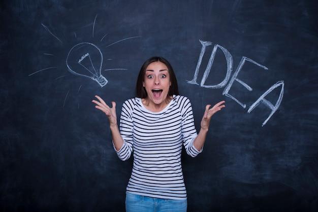 Hermosa joven emocionada está posando sobre un fondo de pizarra con una imagen de idea de lámpara.
