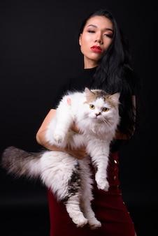 Hermosa joven empresaria asiática contra la pared negra
